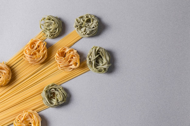 Groene en gele tagliatelle en spaghetti op lichte achtergrond