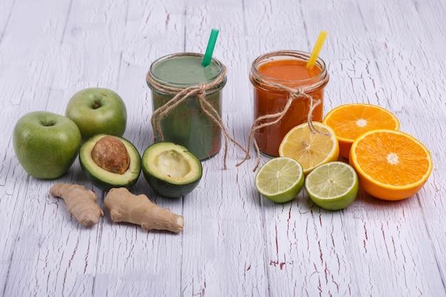 Groene en oranje detox coctails staat op witte tafel met fruit en groenten