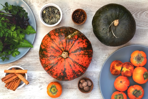 Groene en oranje pompoen, kaki en ingrediënten voor het smakelijke vegetarische koken