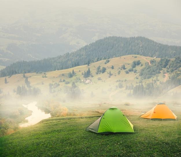 Groene en oranje tenten op vlakte in de bergen op mistige ochtend