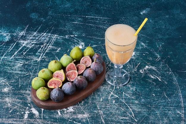 Groene en paarse vijgen met een kopje drank op blauw.