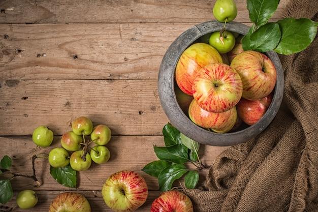 Groene en rode appels op rustieke tafel. plat leggen