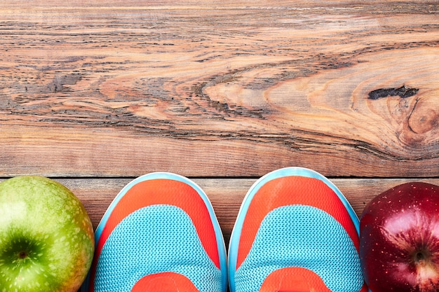 Groene en rode appels. sneakers op houten oppervlak. sport maakt je leven gezond.