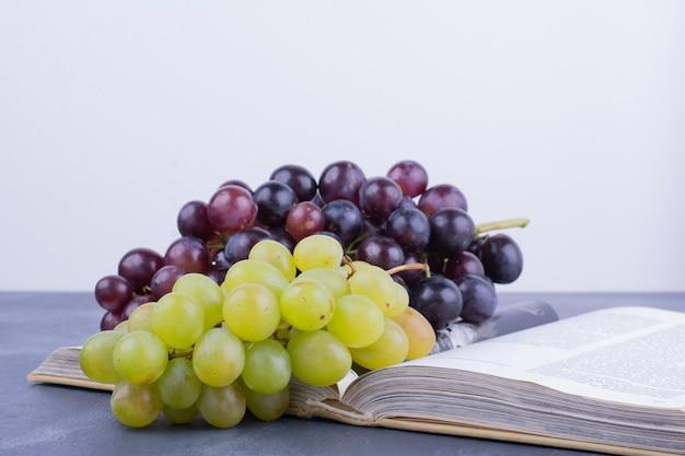 Groene en rode druivenbossen op boek.