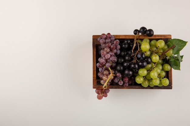 Groene en rode druiventrossen in een houten kist in het midden