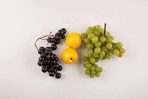 Groene en rode druiventrossen met gele perziken in het midden