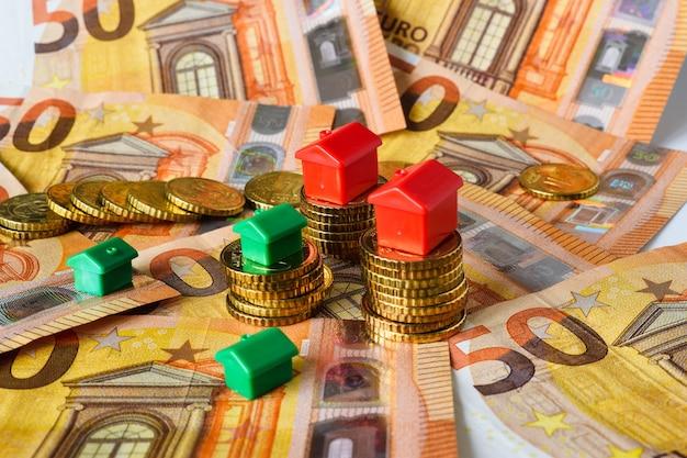 Groene en rode huizen op de achtergrond van eurobankbiljetten en -munten