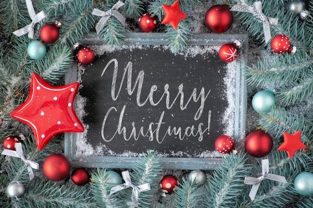 Groene en rode kerstmisachtergrond met verfraaid schoolbord, tekst