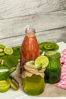 Groene en rode smoothies in een potje met limoen, kiwi