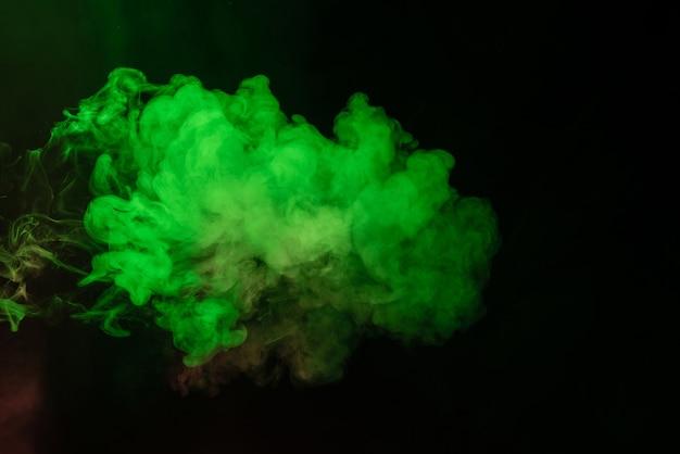 Groene en roze stoom op een zwart oppervlak
