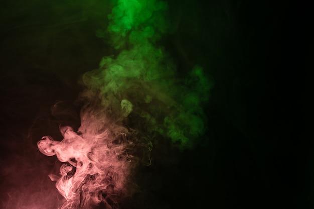 Groene en roze stoom op een zwarte achtergrond. ruimte kopiëren.