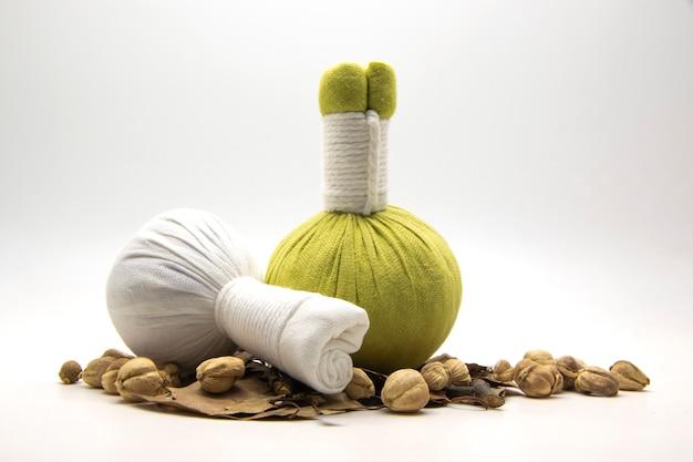 Groene en witte kompresbal met veel kruiden op wit.