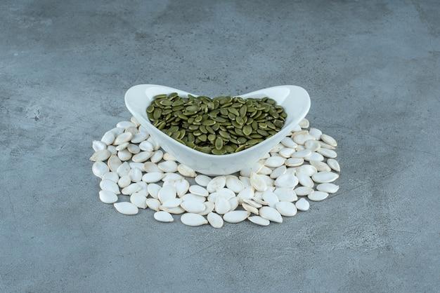 Groene en witte pompoenpitten op blauwe achtergrond. hoge kwaliteit foto