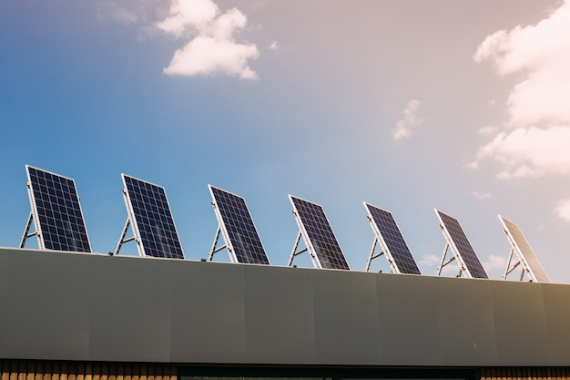 Groene energie van zonnecelpaneel op huisdak in blauwe hemel en zonlicht