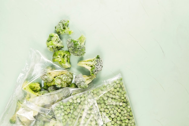 Groene erwten en broccoli in transparante zakken op lichtgroen