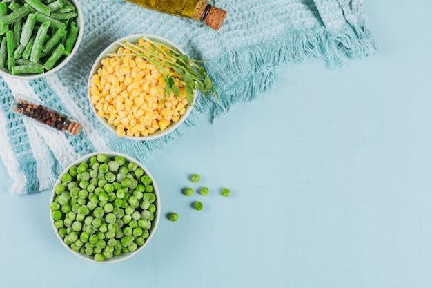 Groene erwten suikermaïs gesneden sperziebonen in kom concept van zelfgemaakte voorbereidingen voor snel koken
