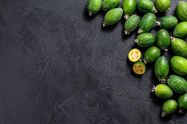 Groene feijoa op zwart bord. bovenaanzicht
