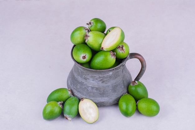 Groene feijoas in een metalen pot op een grijze ondergrond