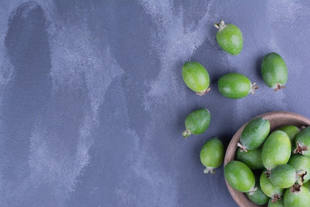 Groene feijoas in een minikopje op blauw.