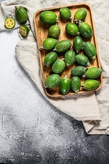 Groene feijoavruchten in een houten plaat op een grijze achtergrond. feijoa van tropisch fruit. bovenaanzicht