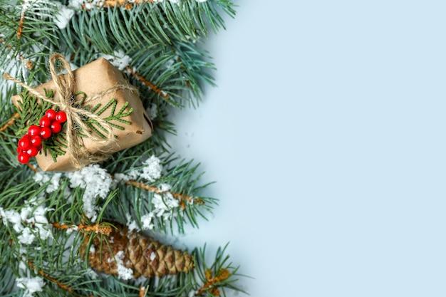 Groene fir takken met kerstcadeau op lichte achtergrond