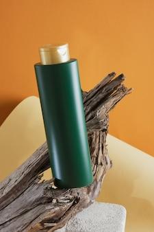 Groene fles voor shampoo of haarbalsem op een betonnen podium op een houten drijfhoutachtergrond, bruine achtergrond, mock-up cosmetica