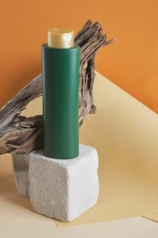 Groene fles voor shampoo of haarbalsem op een betonnen podium op een houten drijfhoutachtergrond, bruine achtergrond