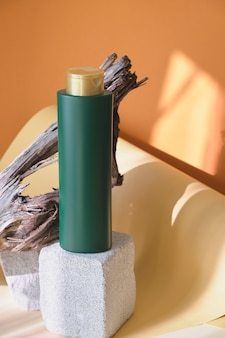 Groene fles voor shampoo of haarbalsem op een betonnen podium tegen een achtergrond van houten drijfhout, bruine achtergrond, zonlicht uit het raam, mooie schaduwen