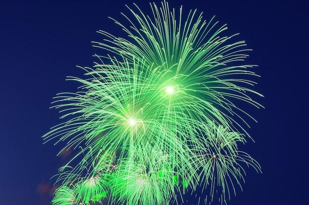 Groene flitsexplosies van saluutschoten in de lucht, met vallende vonken.