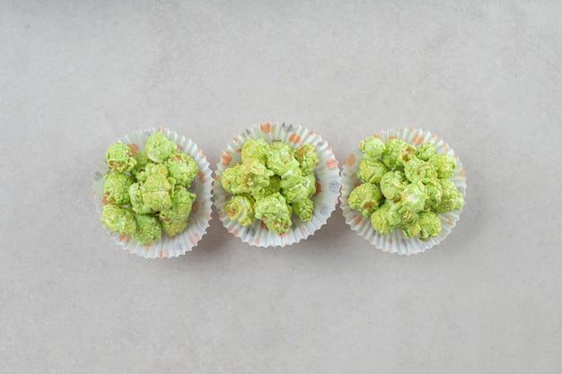 Groene, gekonfijte popcorn werd op marmer in drie pasteitjes gefileerd.