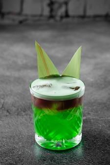 Groene gelaagde cocktail versierd met bamboebladeren op een grijze ondergrond.