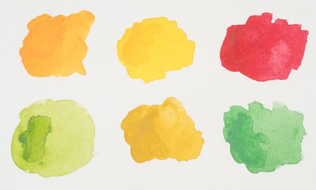 Groene, gele, oranje en rode vlekken van verven op wit papier