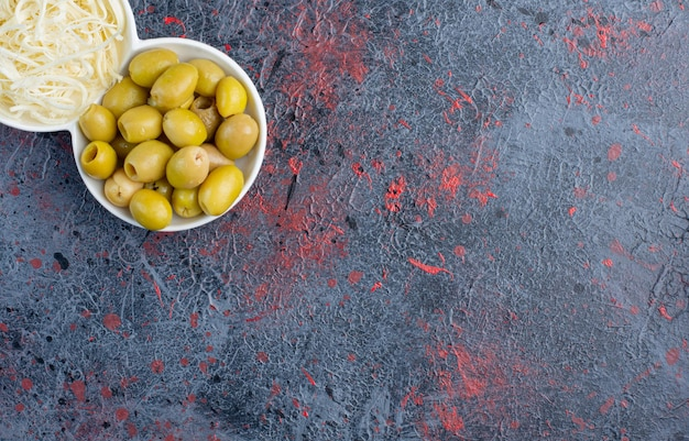 Groene gemarineerde olijven met kaas in witte plaat.