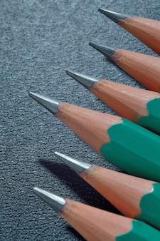 Groene geslepen houten potloden met zwarte stift op een donkere gestructureerde achtergrond. detailopname.