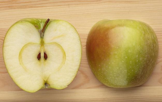 Groene gesneden appel op een houten achtergrond.
