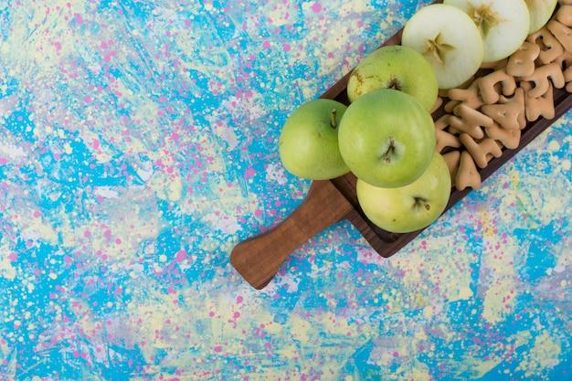 Groene gesneden appels met crackers op het houten bord in de bovenhoek.