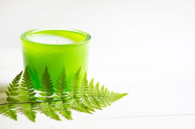 Groene geurkaars met varen en natuurlijke geur op een witte achtergrond. aromatherapie, ontspanning, lichaamsverzorging, harmonie. ruimte kopiëren