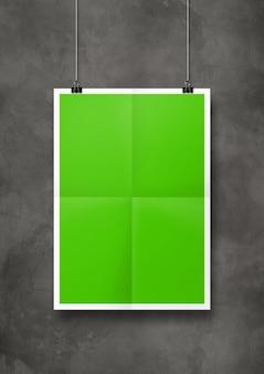 Groene gevouwen poster die met clips aan een betonnen muur hangt.