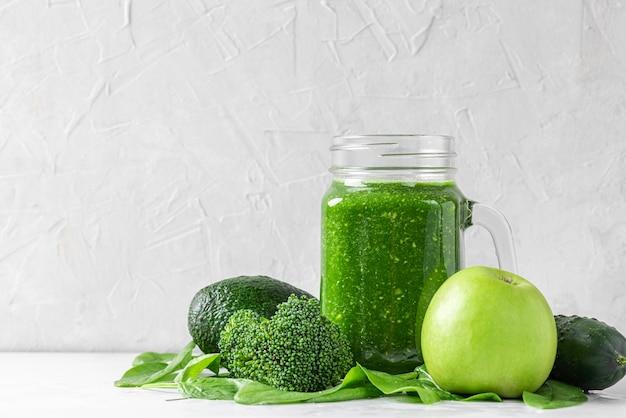 Groene gezonde smoothie in een pot gemaakt van broccoli, spinazie, appel en komkommer. gezond detox-ontbijt. detailopname