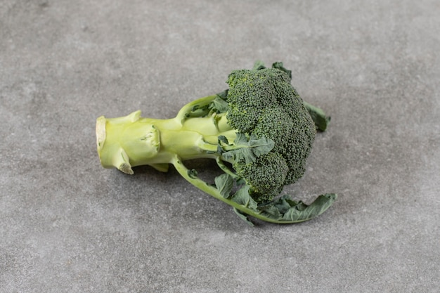 Groene gezonde verse broccoli geplaatst op stenen oppervlak.