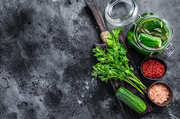 Groene gezouten komkommers. ingeblikte groenten. zwarte achtergrond