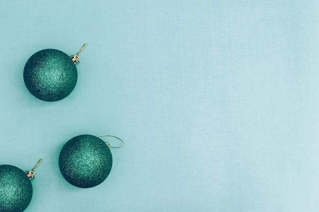 Groene glanzende kerstballen op een blauwe ondergrond