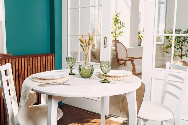Groene glazen en witte gerechten op de ronde keukentafel, met groene plant op de woonkamer op de achtergrond.