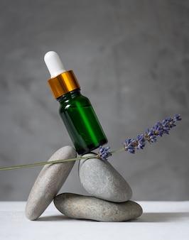 Groene glazen fles en lavendeltak balanceren op stenen.