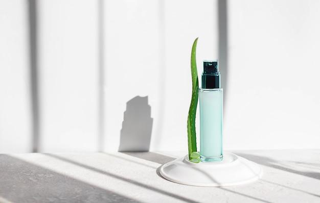 Groene glazen fles mockup met aloë vera bladeren op een lichte achtergrond. natuurlijke en biologische cosmetica. huidverzorging concept voor vrouwen, foto voor sociale netwerken met kopie ruimte.