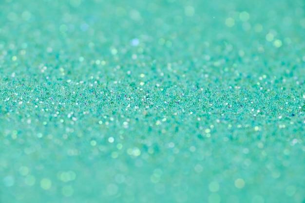 Groene glitter textuur. nieuwjaar of kerstmis achtergrond voor wenskaart. valentijnsdag viering. glanzend sprankelend ontwerp voor feestelijke decoratie: bruiloft, vakantie of jubileumfeest.