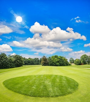 Groene golfbaan en blauwe zonnige hemel. europees veldlandschap