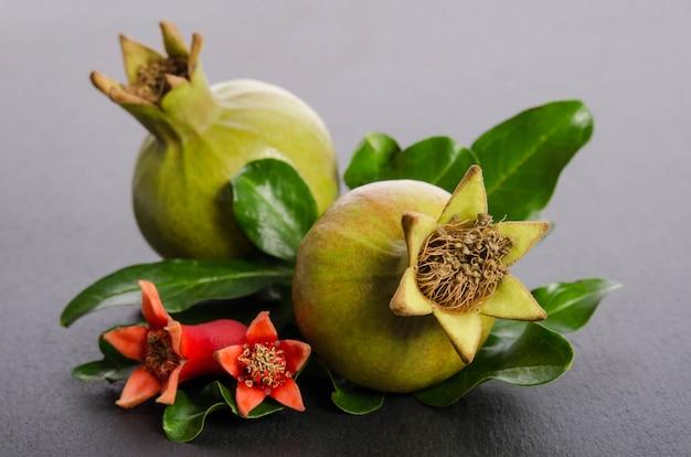 Groene granaatappel met bladeren geïsoleerd op een witte achtergrond