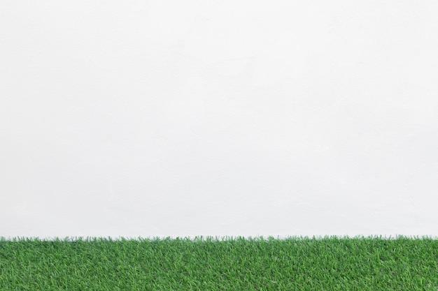 Groene grasvloer met witte concrete achtergrond, model voor ontwerp.
