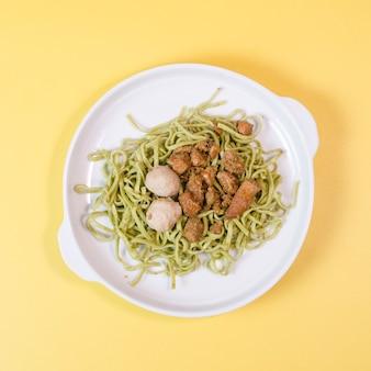 Groene groente noedels in een kom met aziatische gehaktballen en indonesische kip curry